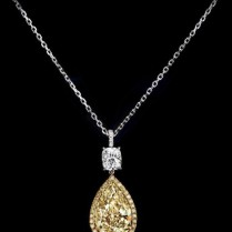5.29-carat fancy pear-shaped diamond with a colorless 0.74 cushion-shaped diamond, accented with yellow and colorless round brilliant diamonds set in platinum.
