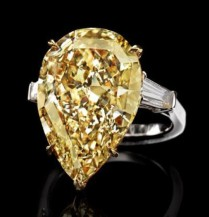 14.07-carat fancy yellow diamond is flanked by two tapered baguette diamonds (0.90tcw) and mounted on platinum and 18k yellow gold.