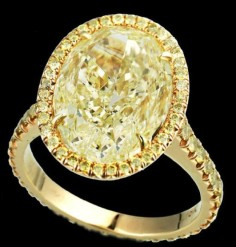 7.06 carats oval-shaped fancy yellow diamond with yellow melee mounted on 18k yellow gold.